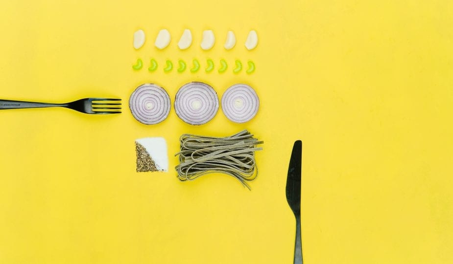 knife, fork and food on yellow background